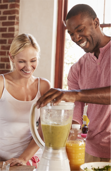 Man and woman using an electric blender to make a smoothie